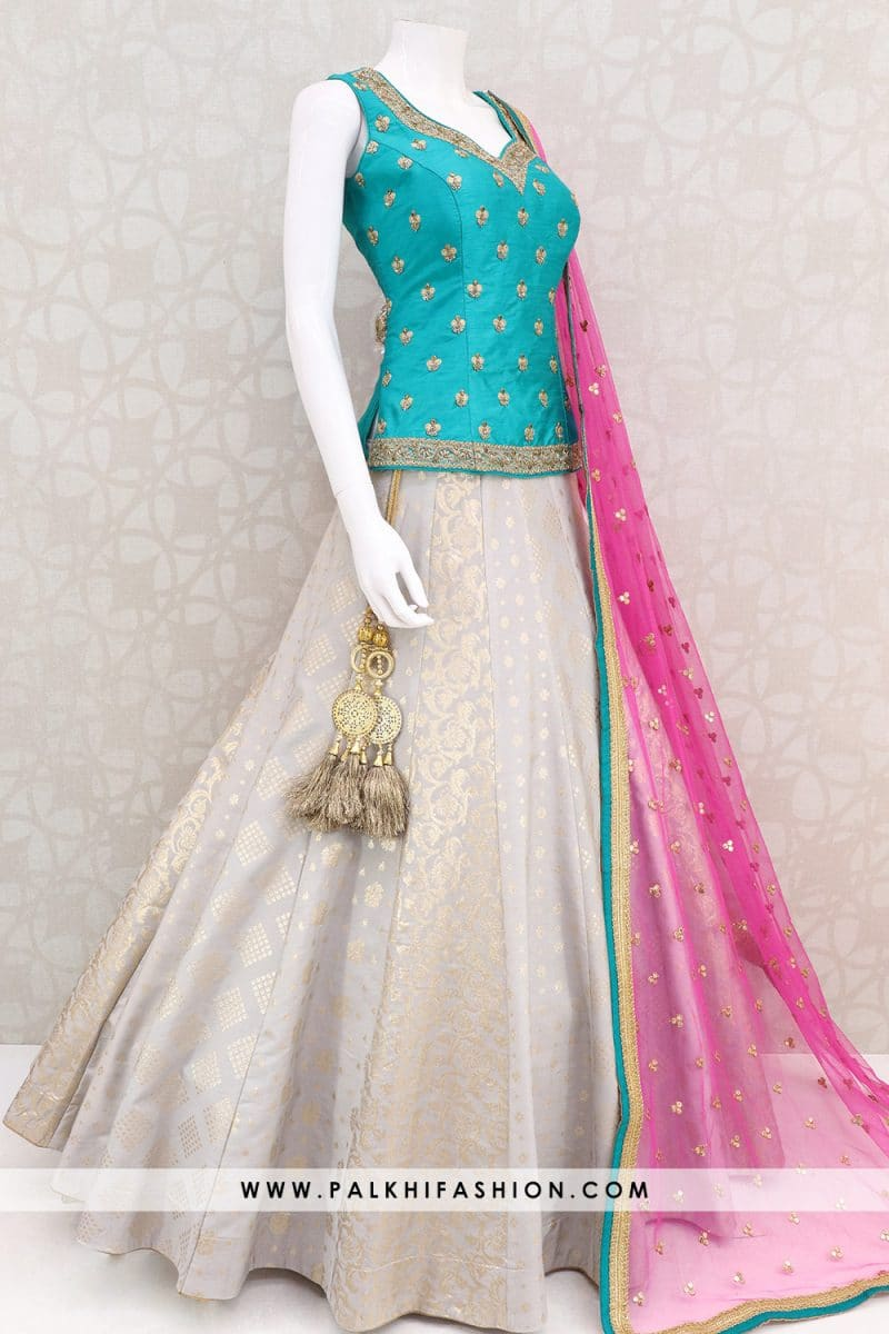 light grey designer lehenga choli from palkhi fashion with silk embossed work.Teal long blouse with deep pink soft net dupatta.Trendy designer lehenga set.